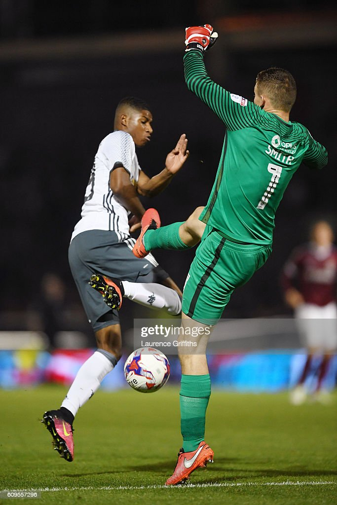 Adam Smith of Northampton Town makes a mistake as Marcus Rashford of Manchester United capitalises to score his sides third goal during the EFL Cup Third Round match between Northampton Town and Manchester United at Sixfields on September 21, 2016 in Northampton, England.