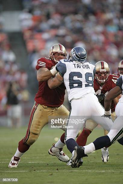 Adam Snyder of the San Francisco 49ers blocks defensive end Joe Tafoya of the Seattle Seahawks during the NFL game at Monster Park on November 20...