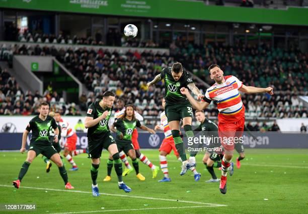 Adam Szalai of 1. FSV Mainz 05 jumps for the ball with Daniel Ginczek of VfL Wolfsburg during the Bundesliga match between VfL Wolfsburg and 1. FSV...