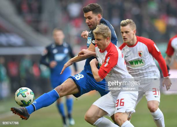 Adam Szalai of Hoffenheim and Martin Hinteregger of Augsburg compete for the ball during the Bundesliga match between FC Augsburg and TSG 1899...