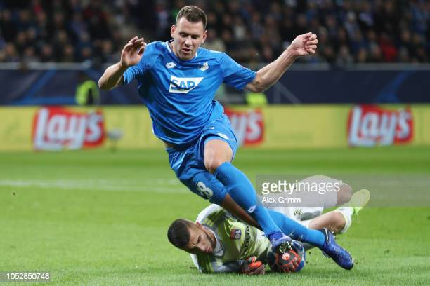 Adam Szalai of Hoffenheim is challenged by goalkeeper Anthony Lopes of Lyon during the Group F match of the UEFA Champions League between TSG 1899...