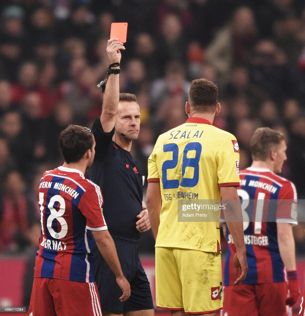 Adam Szalai of Hoffenheim is shown a red card after fouling Dante of Bayern Muenchen during the Bundesliga match between FC Bayern Muenchen and 1899 Hoffenheim at Allianz Arena on November 22, 2014 in Munich, Germany.