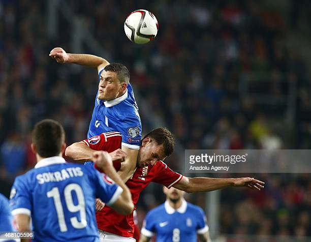 Adam Szalai of Hungary and Kyraiakos Papadopoulos of Greece vie for the ball during their Euro 2016 qualification soccer match at Grupama Arena in...
