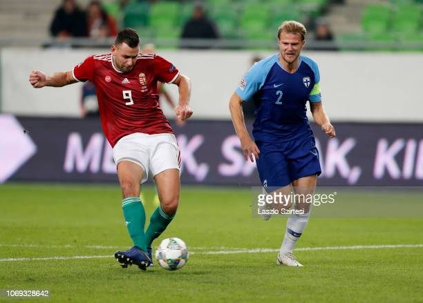 Adam Szalai of Hungary scores the first goal of Hungary next to Paulus Arajuuri of Finland during the UEFA Nations League group stage match between...