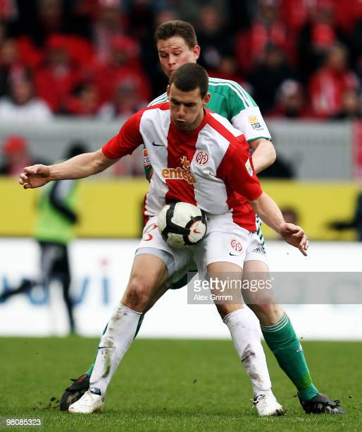 Adam Szalai of Mainz is challenged by Alexander Madlung of Wolfsburg during the Bundesliga match between FSV Mainz 05 and VfL Wolfsburg at the...