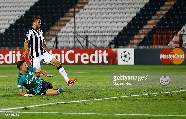 Adam Szalai of Schalke scores his team's first goal as Kostas Katsouranis of PAOK looks on during the UEFA Champions League second leg playoff match...