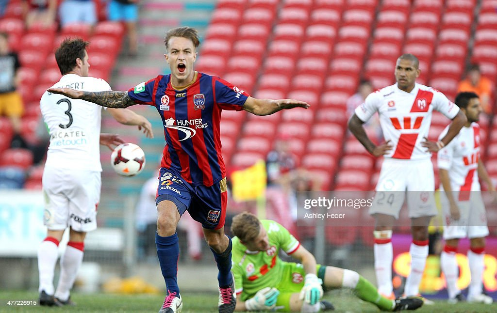 Adam Taggart of the Jets celebrates a goal with Heart players looking dejected during the round 22 A-League match between the Newcastle Jets and Melbourne Heart at Hunter Stadium on March 8, 2014 in Newcastle, Australia.