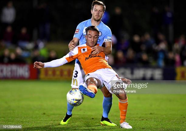 Adam Taggart of the Roar is pressured by the defence of Scott Jamieson of Melbourne City during the FFA Cup round of 32 match between Brisbane Roar...
