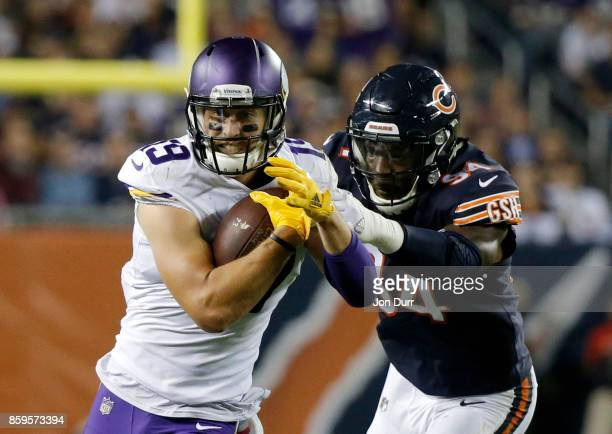 Adam Thielen of the Minnesota Vikings carries the football against Leonard Floyd of the Chicago Bears in the third quarter at Soldier Field on...