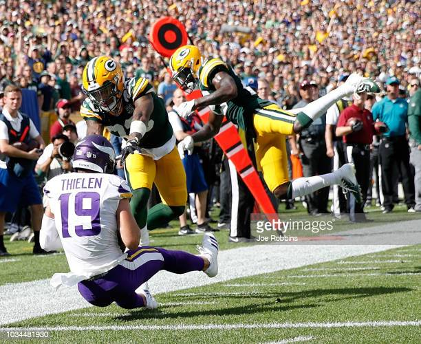 Adam Thielen of the Minnesota Vikings catches a pass for a touchdown in front of Jaire Alexander of the Green Bay Packers and Kentrell Brice during...