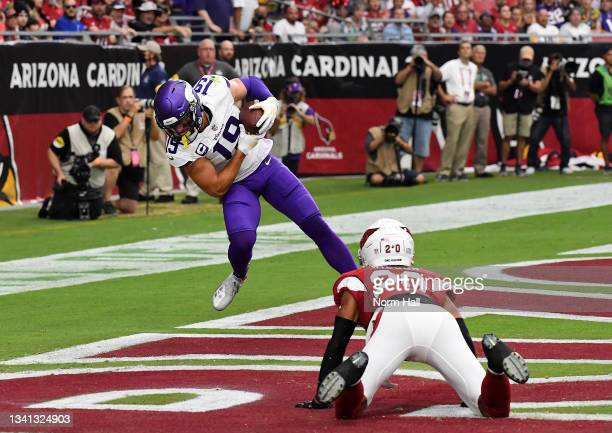 Adam Thielen of the Minnesota Vikings catches a touchdown pass in the end zone as Marco Wilson of the Arizona Cardinals looks on in the first quarter...