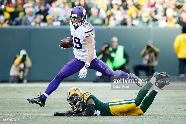 Adam Thielen of the Minnesota Vikings leaps over Quinten Rollins of the Green Bay Packers in the third quarter at Lambeau Field on December 24 2016...