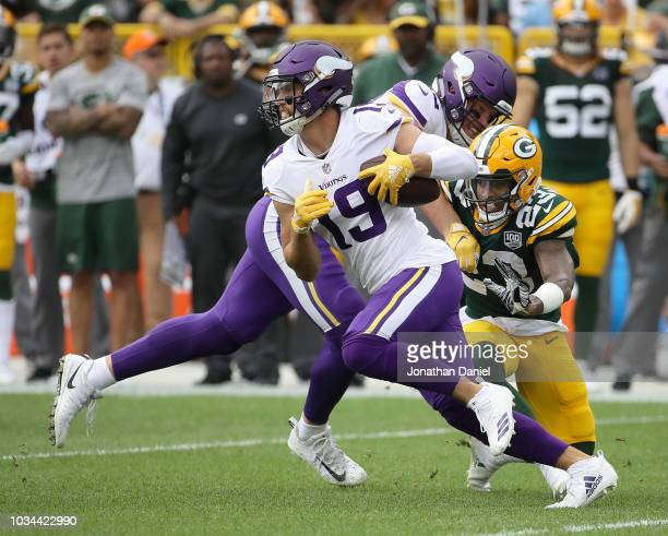 Adam Thielen of the Minnesota Vikings runs past Jaire Alexander of the Green Bay Packers after making a catch during the first quarter of a game at...