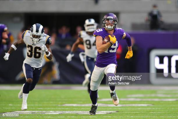Adam Thielen of the Minnesota Vikings runs with the ball away from defender Dominique Hatfield of the Los Angeles Rams of the game on November 19...