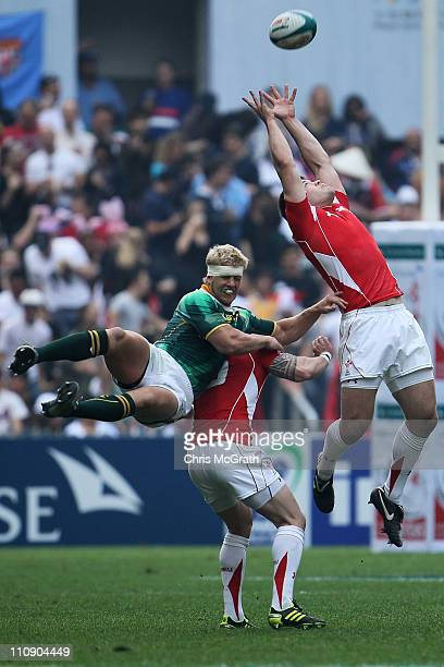 Adam Thomas of Wales makes a catch under pressure from Neil Powell of South Africa during day two of the IRB Sevens at Hong Kong Stadium on March 26,...