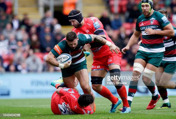 Adam Thompstone of Leicester Tigers is tackled by Rob Webber and Bryn Evans of Sale Sharks during the Gallagher Premiership Rugby match between...