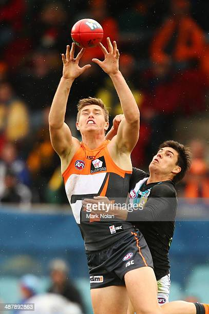 Adam Tomlinson of the Giants and Angus Monfries of the Power contest possession during the round seven AFL match between the Greater Western Sydney...
