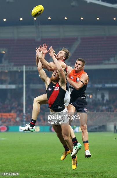 Adam Tomlinson of the Giants competes for the ball against Dyson Heppell and James Stewart of the Bombers during the round 10 AFL match between the...