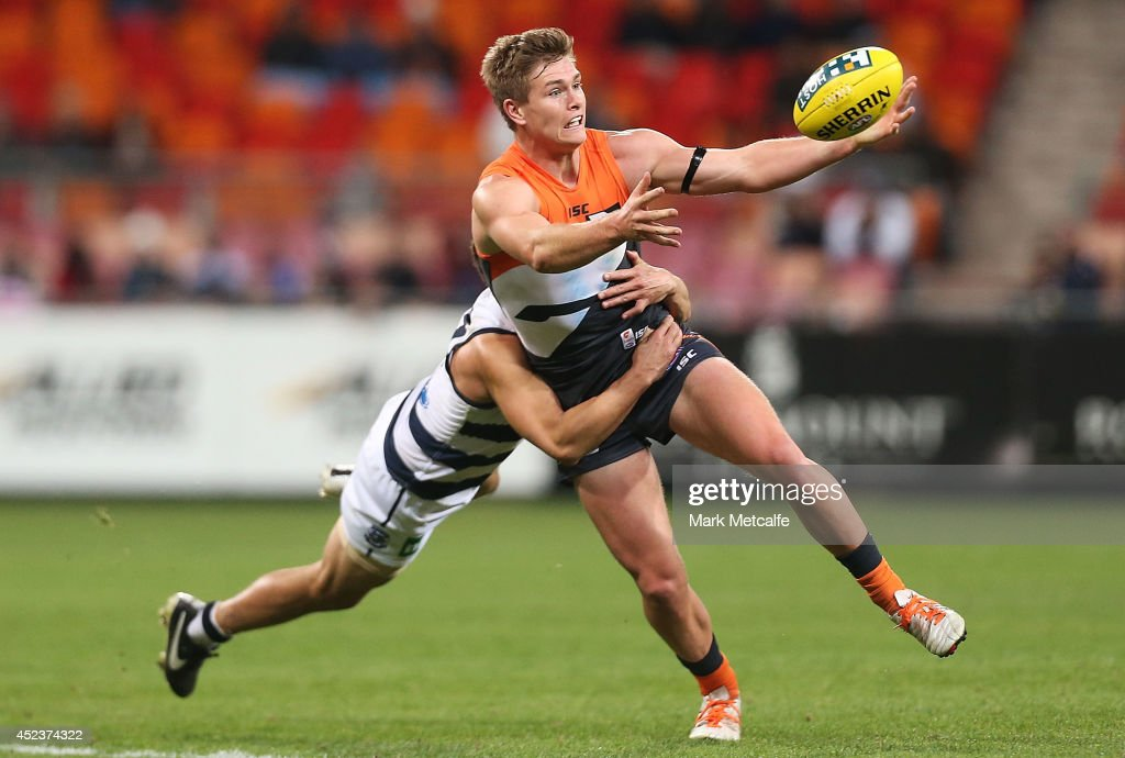 Adam Tomlinson of the Giants is tackled by Mathew Stokes of the Cats during the round 18 AFL match between the Greater Western Sydney Giants and the Geelong Cats at Spotless Stadium on July 19, 2014 in Sydney, Australia.