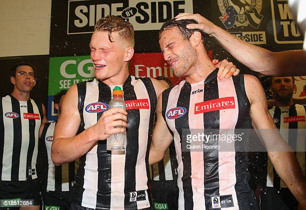 Adam Treloar and James Aish of the Magpies are sprayed with drinks as the Magpies sing the song after winning the round two AFL match between the...