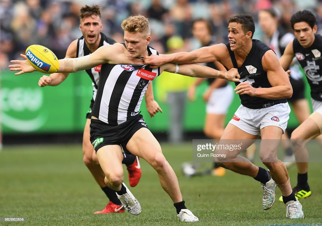 Adam Treloar of the Magpies and Ed Curnow of the Blues compete for the ball during the round 14 AFL match between the Collingwood Magpies and the Carlton Blues at Melbourne Cricket Ground on June 24, 2018 in Melbourne, Australia.