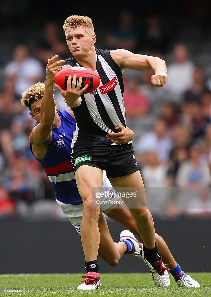 Adam Treloar of the Magpies handballs whilst being tackled by Jason Johannisen of the Bulldogs during the 2016 NAB Challenge AFL match between the Collingwood Magpies and the Western Bulldogs at Etihad Stadium on March 12, 2016 in Melbourne, Australia.