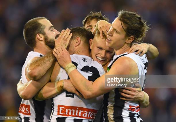 Adam Treloar of the Magpies is congratulated by team mates after kicking a goal during the round 12 AFL match between the Melbourne Demons and the...