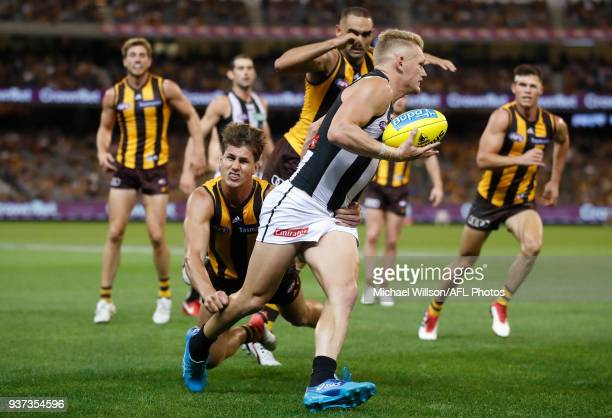 Adam Treloar of the Magpies is tackled by Daniel Howe of the Hawks during the 2018 AFL round 01 match between the Hawthorn Hawks and the Collingwood...