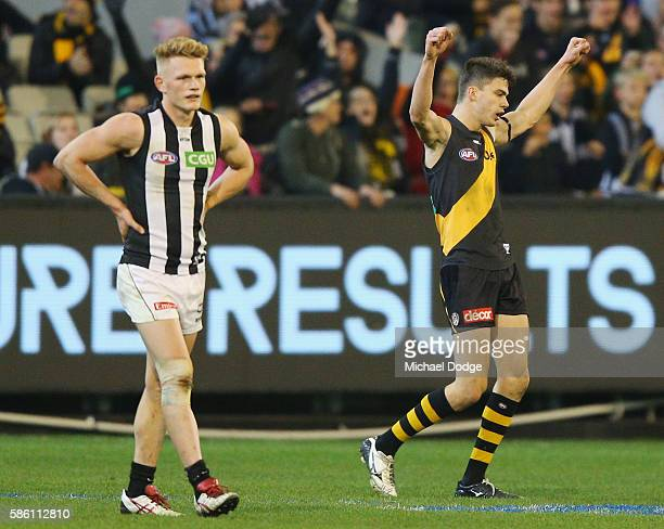Adam Treloar of the Magpies looks dejected after defeat as Oleg Markov of the Tigers celebrates the win during the round 20 AFL match between the...