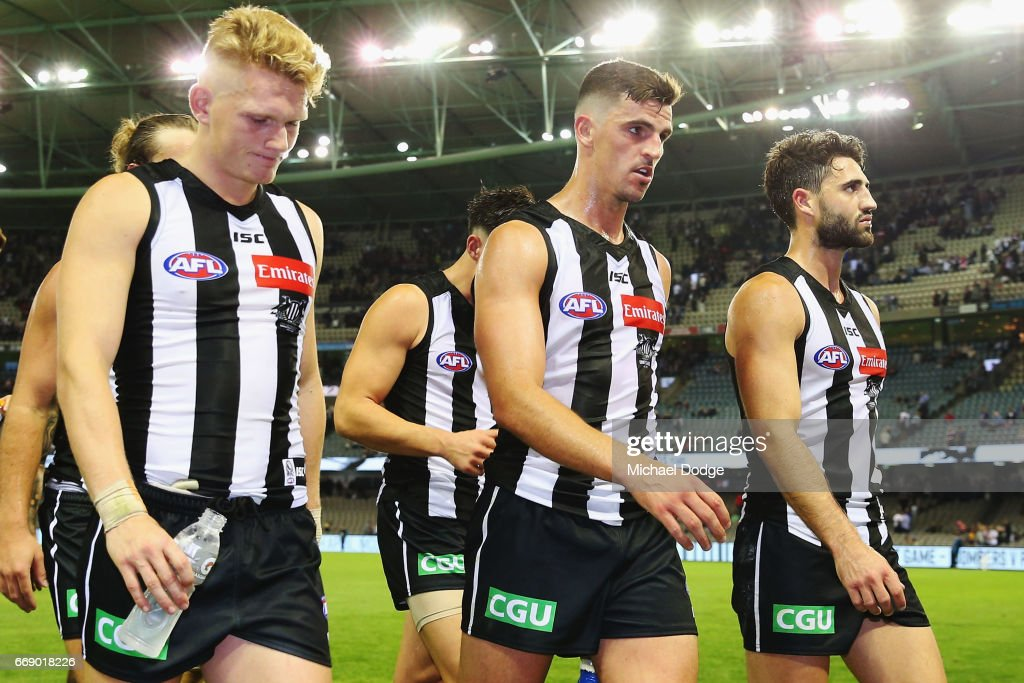 Adam Treloar (L) Scott Pendlebury (C) and Alex Fasolo of the Magpies looks dejected after defeat during the round four AFL match between the Collingwood Magpies and the St Kilda Saints at Etihad Stadium on April 16, 2017 in Melbourne, Australia.