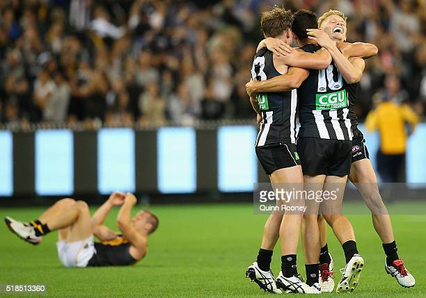 Adam Treloar Taylor Adams and Scott Pendlebury of the Magpies celebrate winning as Kane Lambert of the Tigers looks dejected during the round two AFL...