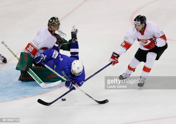 Adam Vay of Hungary, Andrej Hebar of Slovenia and Bence Sziranyi of Hungary in action during the 2018 IIHF Ice Hockey World Championship Division I...