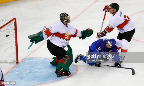 Adam Vay of Hungary cannot catch the puck next to Tommaso Traversa of Italy and Kevin Wehrs of Hungary during the 2018 IIHF Ice Hockey World...