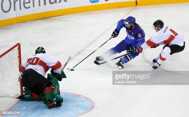 Adam Vay of Hungary watches Giulio Scandella of Italy and Tamas Pozsgai of Hungary behind during the 2018 IIHF Ice Hockey World Championship Division...