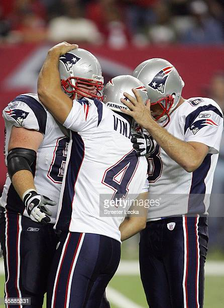 Adam Vinatieri celebrates with teammates Dan Koppen and Josh Miller of the New England Patriots after kicking the game winning field goal to defeate...