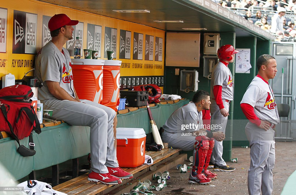 Adam Wainwright #50, Yadier Molina #4, and Daniel Descalso #33 of the St. Louis Cardinals look on from the dugout during the game against the Pittsburgh Pirates at PNC Park April 6, 2014 in Pittsburgh, Pennsylvania. The Pirates defeated the Cardinals 2-1.