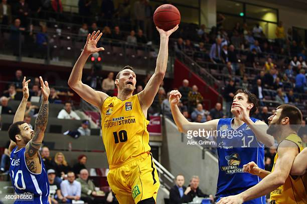 Adam Waleskowski of Ludwigsburg tries to score against Justin Cobbs and Johannes Voigtmann of Frankfurt during the Beko BBL basketball match between...