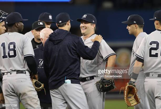 Adam Warren of the New York Yankees is examined by manager Aaron Boone before leaving the game after being hit by a line drive grounder in the sixth...