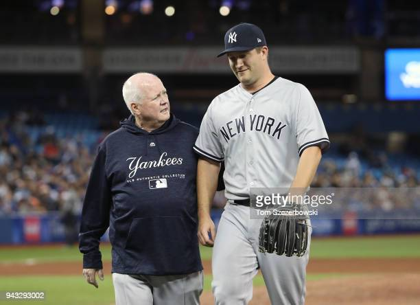 Adam Warren of the New York Yankees walks off the field with head trainer Steve Donohue due to injury in the sixth inning during MLB game action...