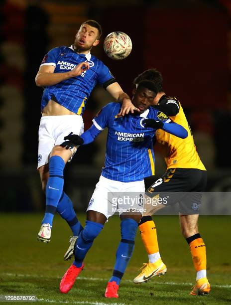 Adam Webster and Yves Bissouma of Brighton and Hove Albion compete for a header with Padraig Amond of Newport County during the FA Cup Third Round...