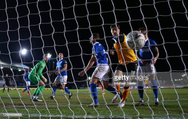 Adam Webster of Brighton and Hove Albion scores an own goal for Newport County's first goal under pressure from Jamie Proctor of Newport County...