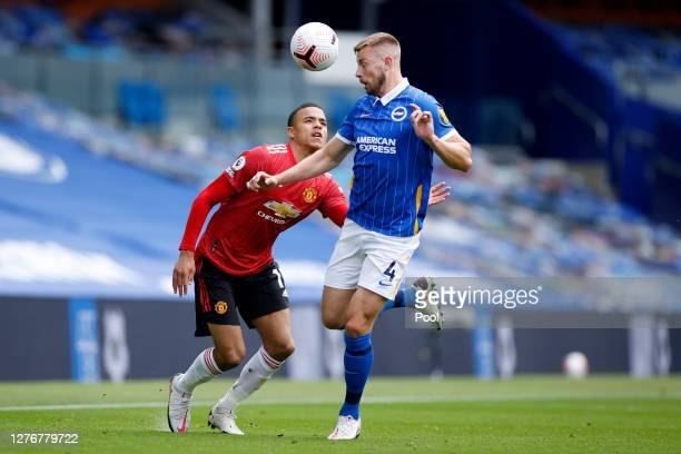 Adam Webster of Brighton and Hove Albion wins a header from Mason Greenwood of Manchester United during the Premier League match between Brighton...