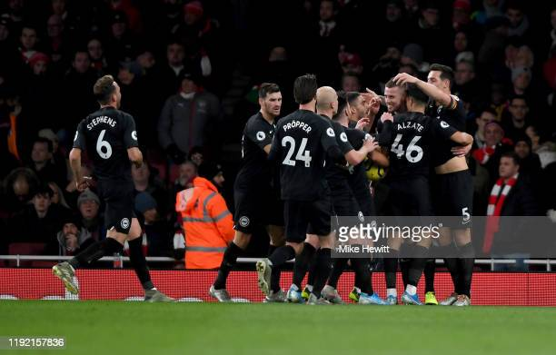 Adam Webster of Brighton celebrates with team mates after scoring his teams first goal during the Premier League match between Arsenal FC and...
