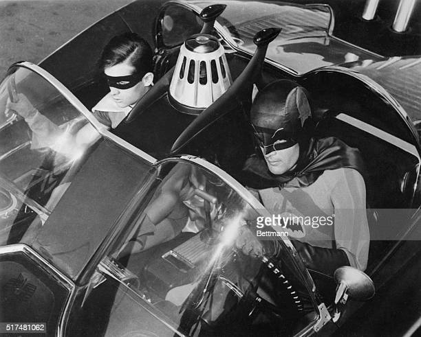 "Adam West, and Burt Ward are shown as their television characters, ""Batman"" and Robin."" They are shown in the ""Batmobile."" This is a still photo from..."