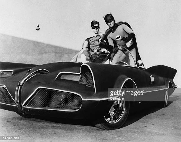 Adam West and Burt Ward as Batman and Robin atop the Batmobile in the famously campy TV series Batman early in the show's run in 1966