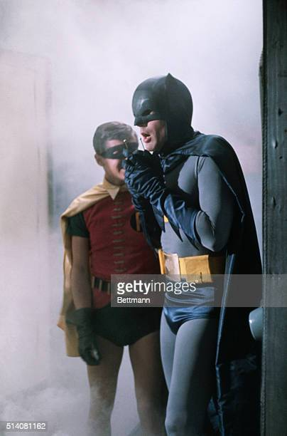 Adam West as Batman speaks into his phone while Burt Ward as Robin looks on in a scene from the television show, Batman.