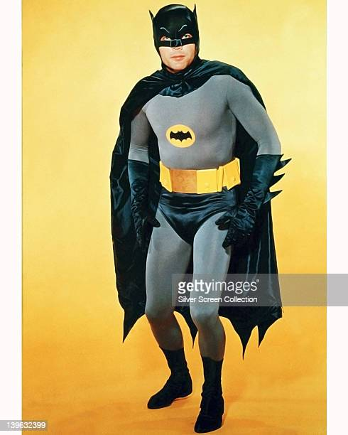 Adam West US actor in costume in a studio portrait against a yellow background issued as publicity for the television series 'Batman' USA circa 1966...