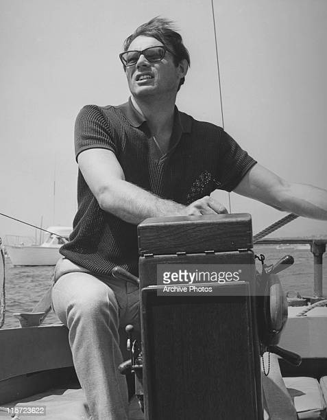 Adam West US actor wearing sunglasses as he sits at the ship's wheel of a yacht USA circa 1965 West is best known for playing the lead role in the...