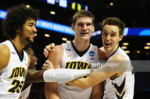 Adam Woodbury celebrates scoring the game winning goal with Dom Uhl and Nicholas Baer of the Iowa Hawkeyes in overtime against the Temple Owls during...