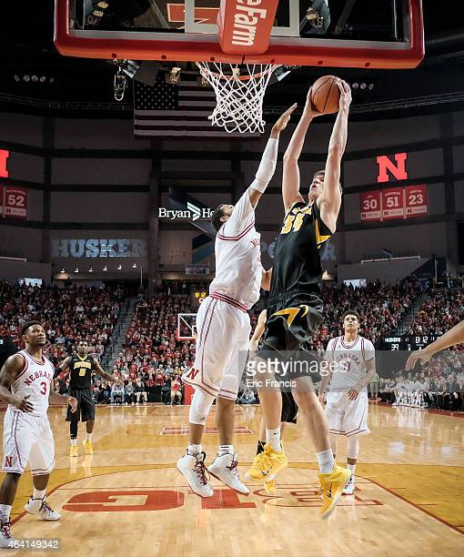 Adam Woodbury of the Iowa Hawkeyes drives to the basket over Walter Pitchford of the Nebraska Cornhuskers during their game at Pinnacle Bank Arena...